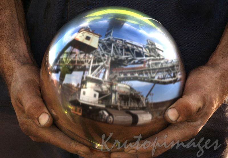 maintenance, mans hands with large ball bearing from mine dredge.